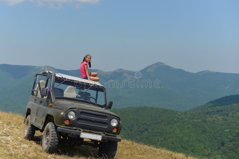 Nastoletniej dziewczyny obsiadanie na dachu SUV w górach zdjęcie royalty free