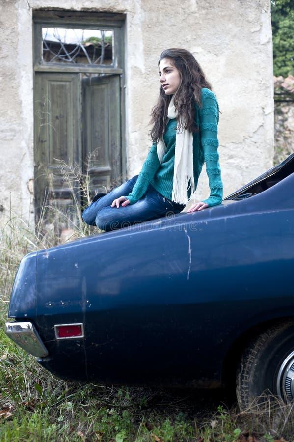 Nastoletniej dziewczyny obsiadanie na samochodzie obrazy stock
