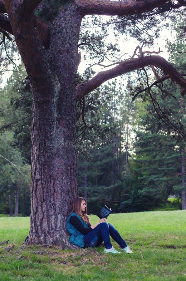 Nastoletniej dziewczyny obsiadanie pod czytelniczą książką i drzewem obrazy stock