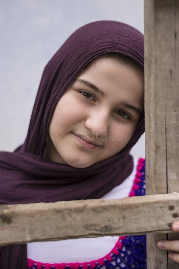Nastoletniej dziewczyny pozycja w plecy jest ubranym tradycyjnego trykotowego płótno z białą chustą przed barwioną ścianą drewnia obraz stock