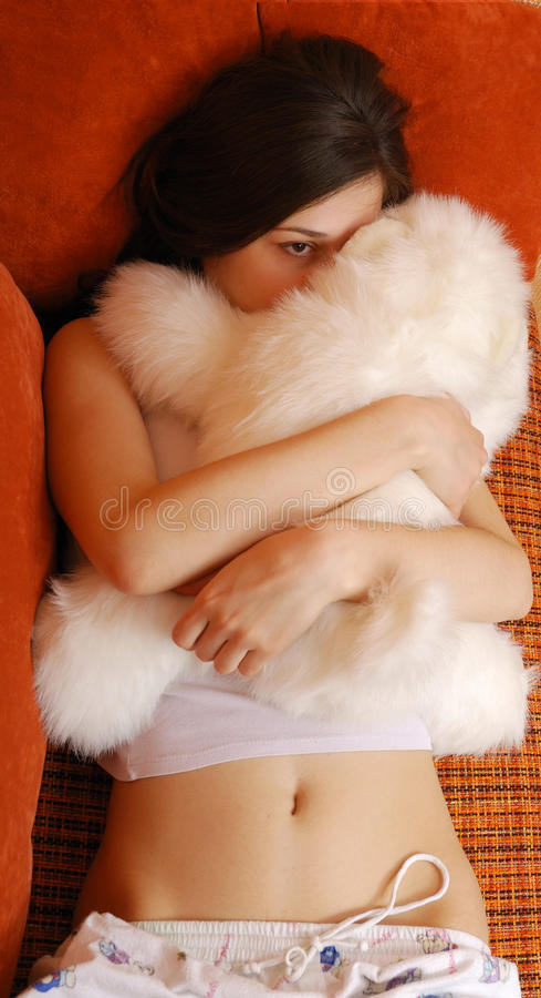 Nastoletniej dziewczyny przytulenie z milutką zabawką w kanapy łóżku fotografia royalty free