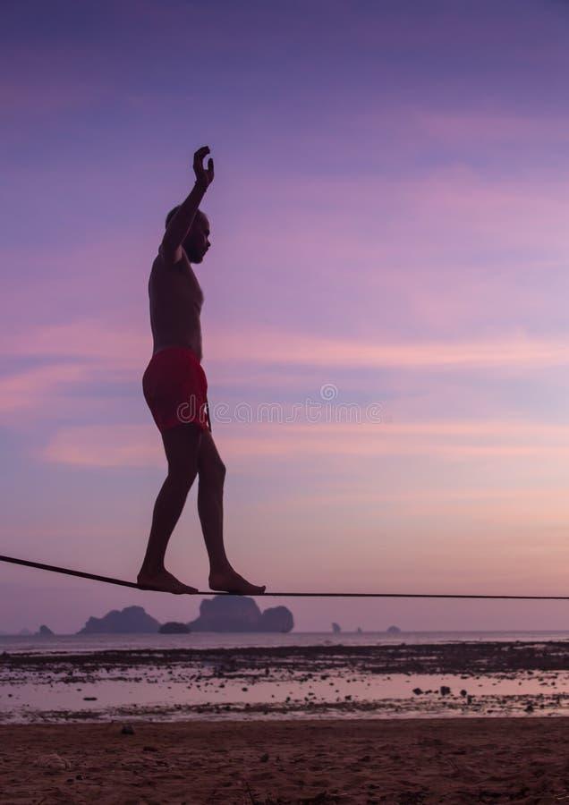 Nastoletniej dziewczyny równoważenie na slackline z niebo widokiem na plaży obrazy royalty free