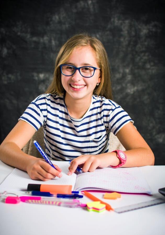 Nastoletniej dziewczyny wyko?czeniowa praca domowa w domu obraz royalty free