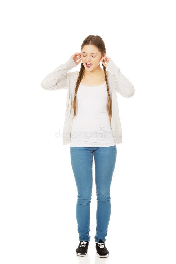 Nastoletniej kobiety nakrywkowi ucho z palcami obraz stock