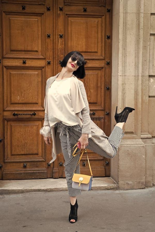 nastrój figlarne Dziewczyny modna dama z koczek fryzury architektury plenerowym miastowym tłem Kobieta modny model zdjęcie royalty free