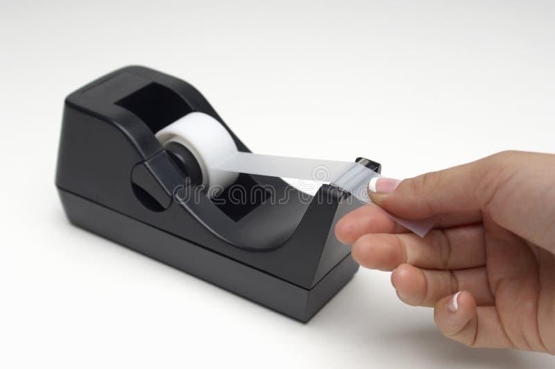 Nastro adesivo del taglio manuale dal supporto fotografia stock libera da diritti