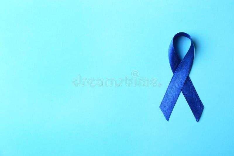 Nastro blu sul fondo di colore, vista superiore Concetto di consapevolezza del tumore del colon immagini stock libere da diritti