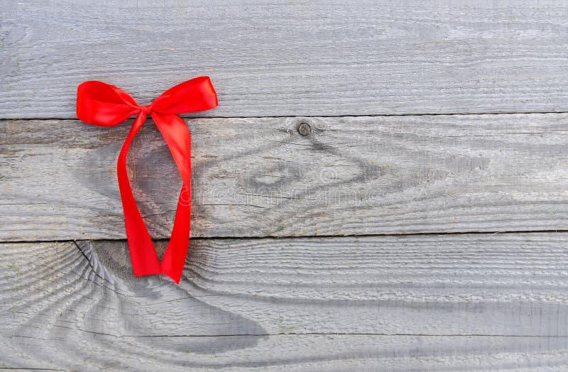 Nastro decorativo rosso con l'arco sul vecchio fondo dei bordi di legno fotografia stock libera da diritti