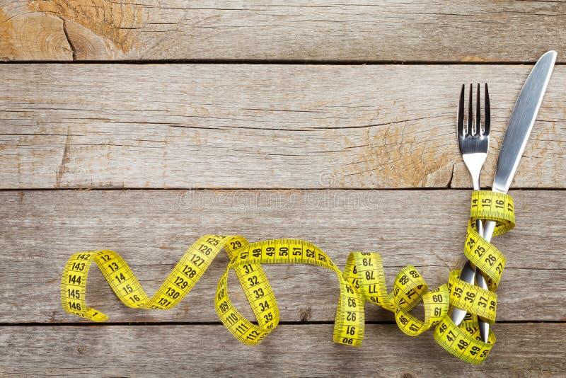 Nastro di misura con il coltello e la forcella Stia l'alimento a dieta immagini stock