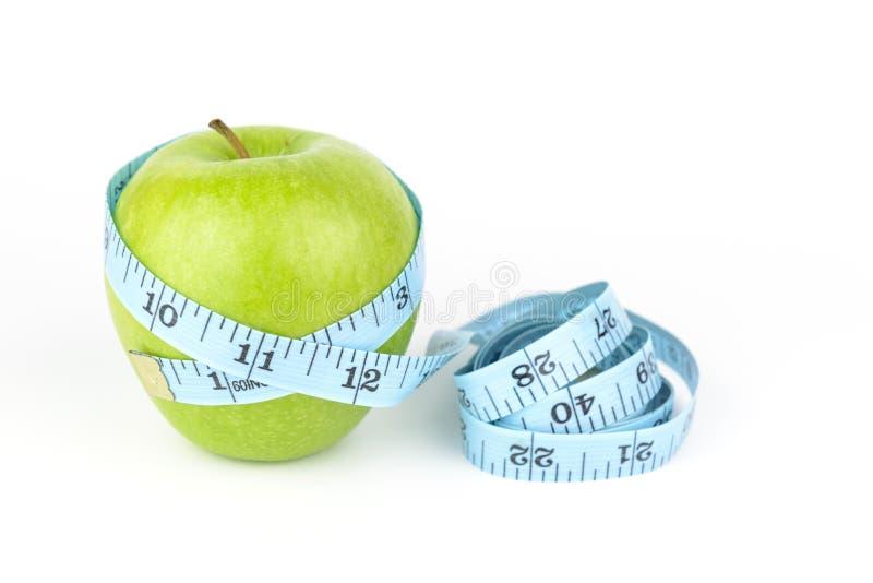 Nastro di misura e mela verde, fondo bianco immagini stock