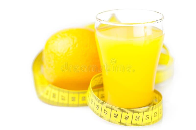 Nastro di misurazione, arancia e un vetro di succo d'arancia immagine stock libera da diritti