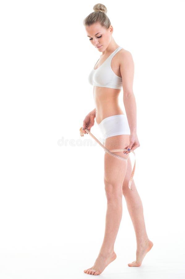 Nastro di misurazione di misurazione della vita della giovane donna atletica, OV isolato immagini stock libere da diritti