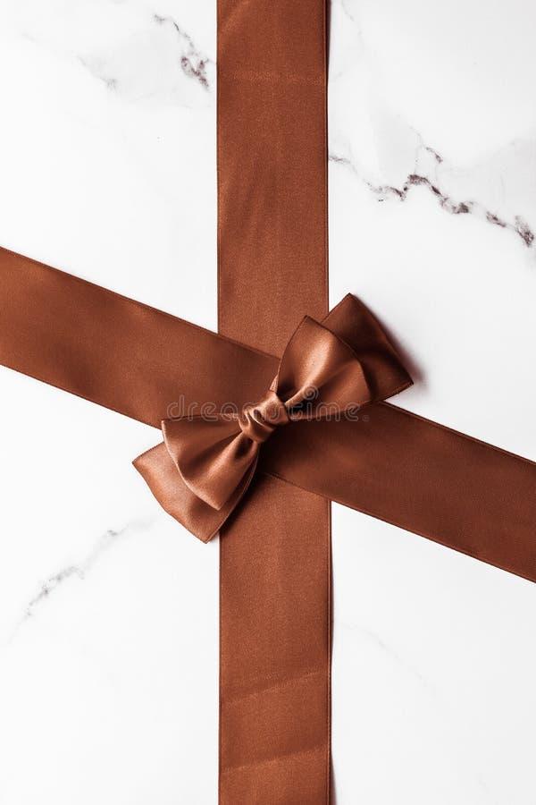 Nastro di seta color cioccolato su fondo di marmo, flatlay immagini stock