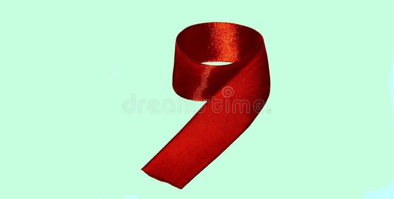 Nastro di seta rosso piegato sotto forma dei nove fotografia stock libera da diritti