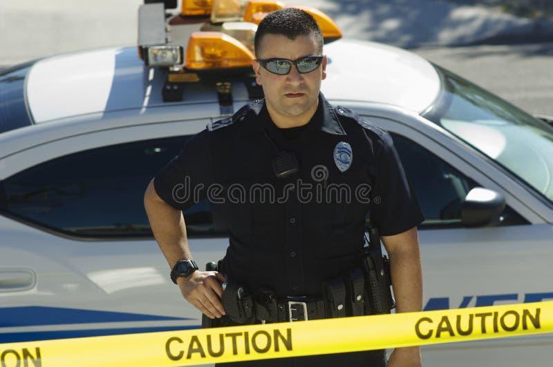 Nastro di Standing Behind Caution dell'ufficiale di polizia immagini stock libere da diritti