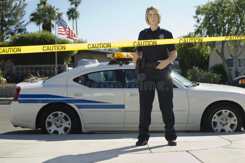 Nastro di Standing Behind Caution dell'ufficiale di polizia fotografia stock libera da diritti