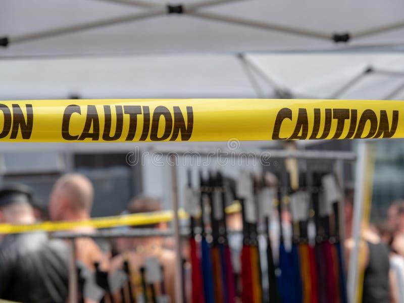 Nastro giallo di cautela che appende davanti al deposito di BDSM con le fruste immagini stock libere da diritti