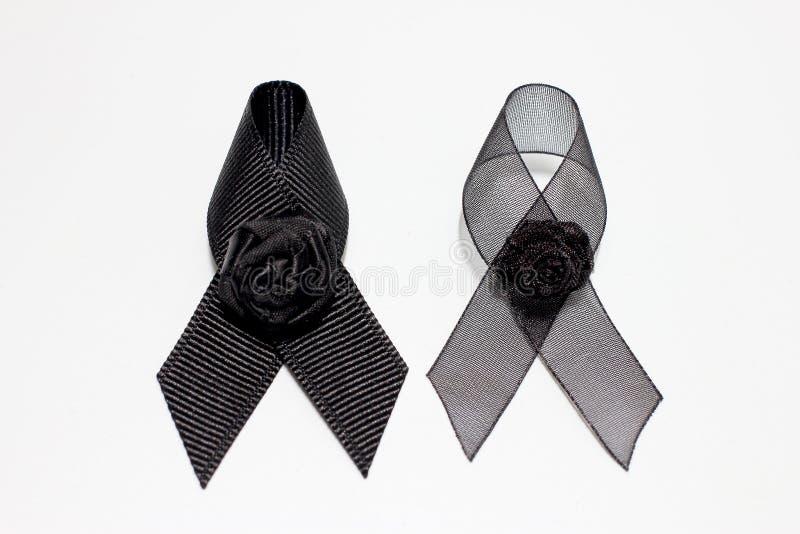 Nastro nero; progettazione artistica fatta a mano del nastro nero della decorazione per l'espressione di tristezza isolata su fon fotografia stock