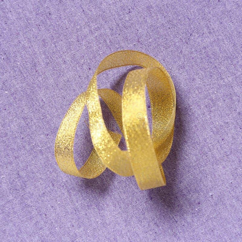 Nastro riccio dell'oro sul fondo del tessuto fotografia stock