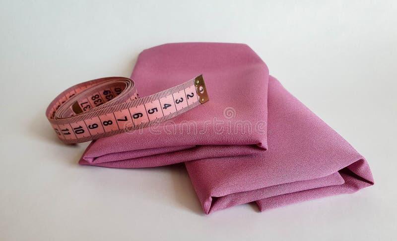 Nastro rosa di misura con i numeri neri su un fondo bianco del tessuto o naturale Vista alta vicina del nastro di misurazione fotografie stock libere da diritti