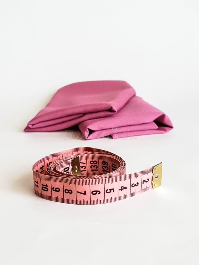 Nastro rosa di misura con i numeri neri su un fondo bianco del tessuto o naturale Vista alta vicina del nastro di misurazione Tem fotografie stock