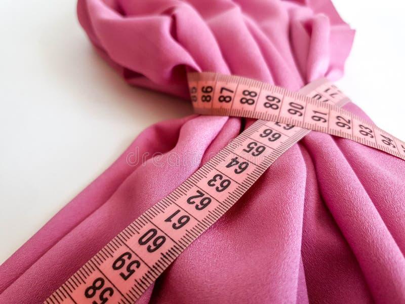 Nastro rosa di misura con i numeri neri su un fondo bianco del tessuto o naturale Vista alta vicina del nastro di misurazione Tem immagine stock