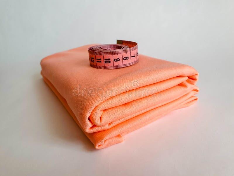 Nastro rosa di misura con i numeri neri su un fondo bianco del tessuto o naturale Vista alta vicina del nastro di misurazione Tem fotografia stock libera da diritti