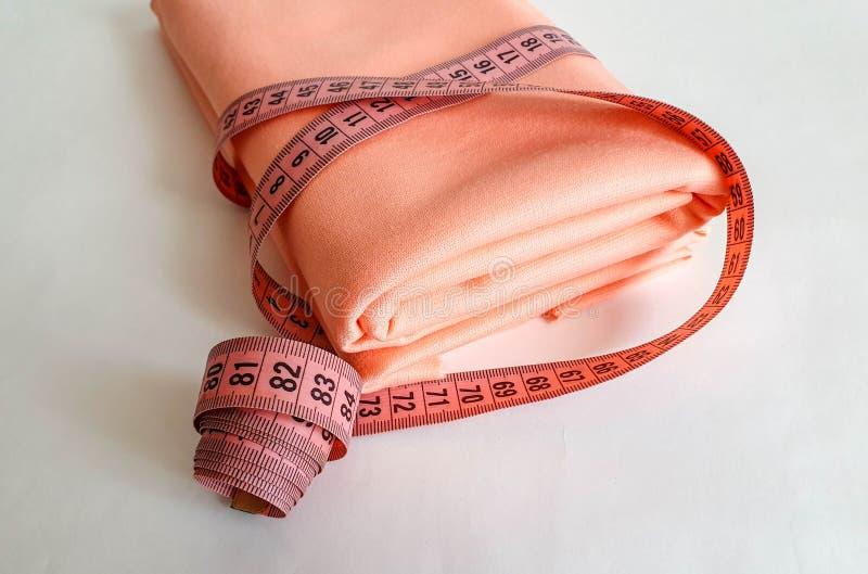 Nastro rosa di misura con i numeri neri su un fondo bianco del tessuto o naturale Vista alta vicina del nastro di misurazione Tem immagine stock libera da diritti