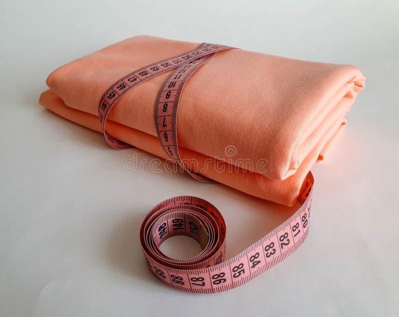 Nastro rosa di misura con i numeri neri su un fondo bianco del tessuto o naturale Vista alta vicina del nastro di misurazione Tem fotografia stock