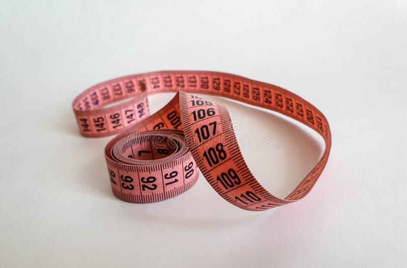 Nastro rosa di misura con i numeri neri su uno sfondo naturale bianco Chiuda su del nastro di misurazione Temi: dieta, fatta a ma immagini stock