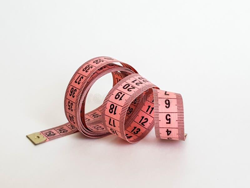 Nastro rosa di misura con i numeri neri su uno sfondo naturale bianco Chiuda su del nastro di misurazione Temi: dieta, fatta a ma immagine stock libera da diritti