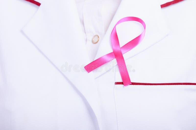 Nastro rosa sul grembiule medico bianco fotografia stock