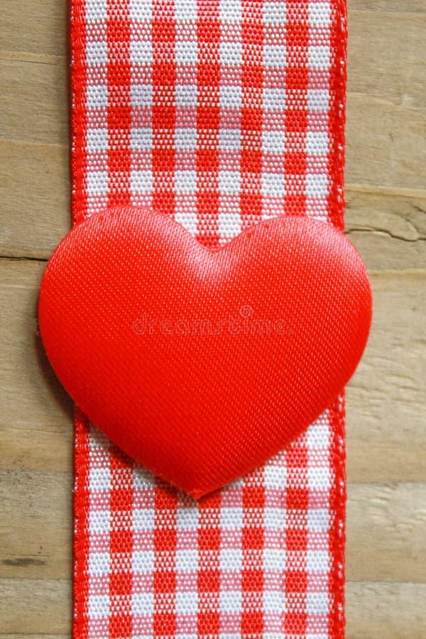 Nastro rosso del percalle e un cuore di amore fotografia stock