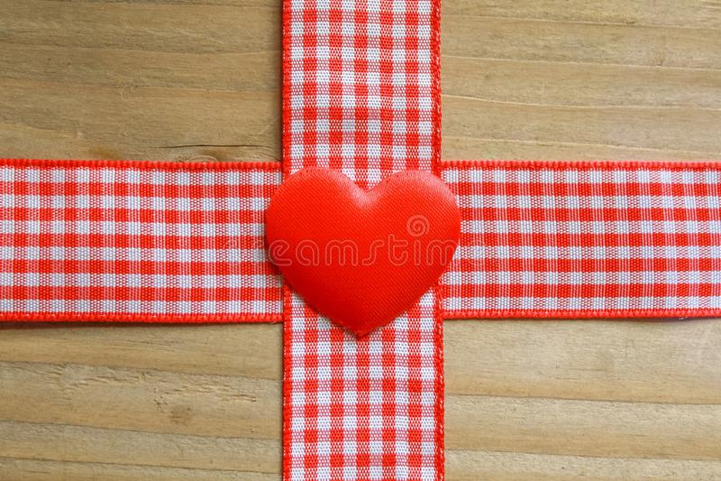 Nastro rosso del percalle e un cuore di amore immagini stock libere da diritti