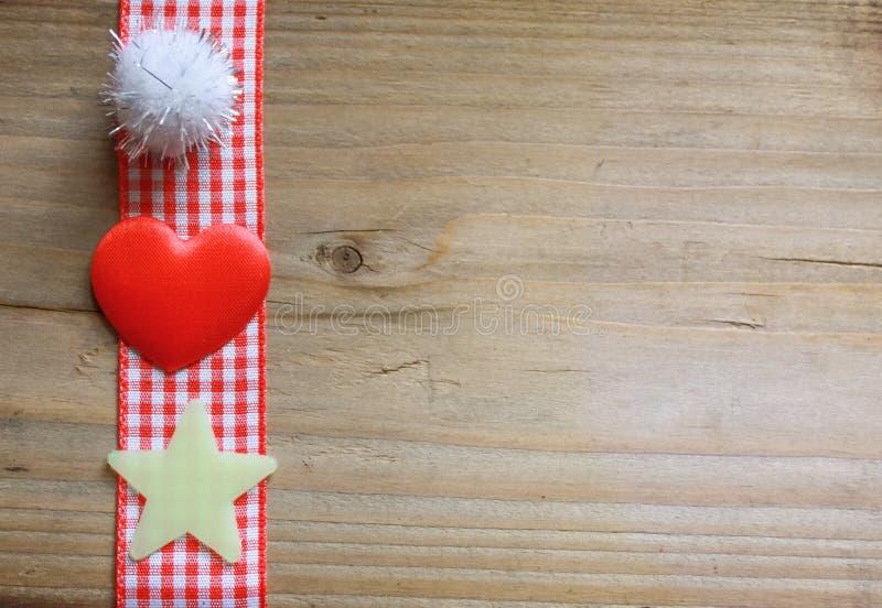 Nastro rosso del percalle, una palla lanuginosa, una stella e un cuore di amore immagini stock