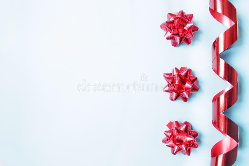 Nastro rosso del serpentino, archi rossi festivi, gruppo del pacchetto, fondo della cartolina d'auguri isolato su fondo blu fotografie stock libere da diritti