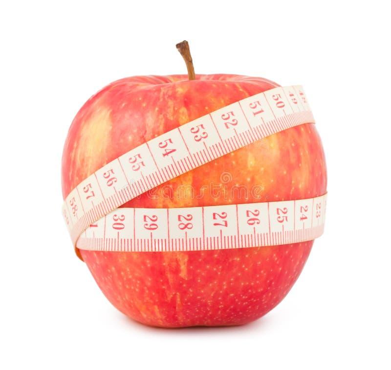 Nastro rosso di misura e della mela fotografie stock