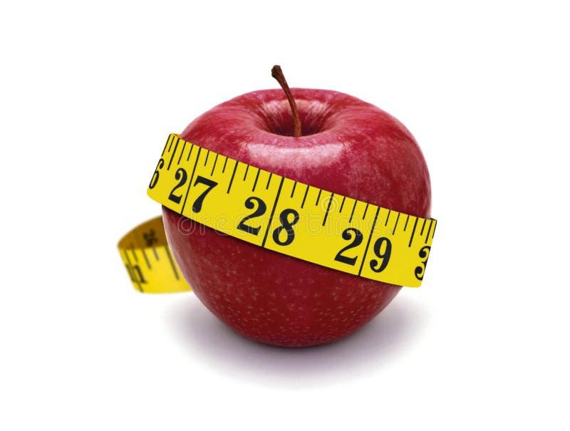 Nastro rosso di misura e della mela fotografia stock libera da diritti