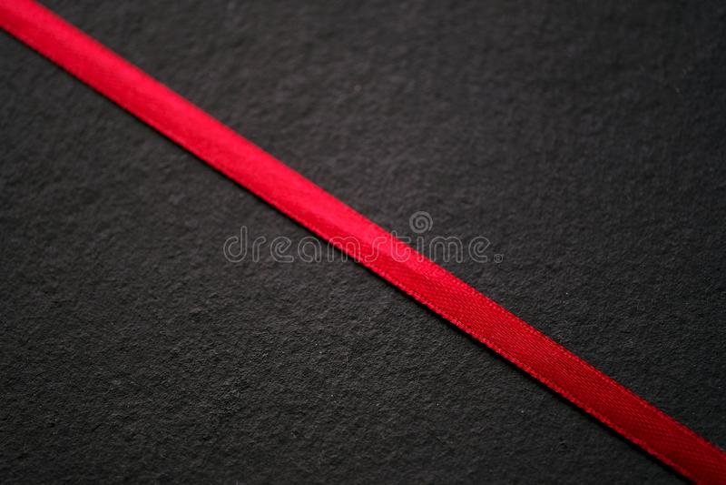 Nastro rosso sul nero, struttura immagine stock