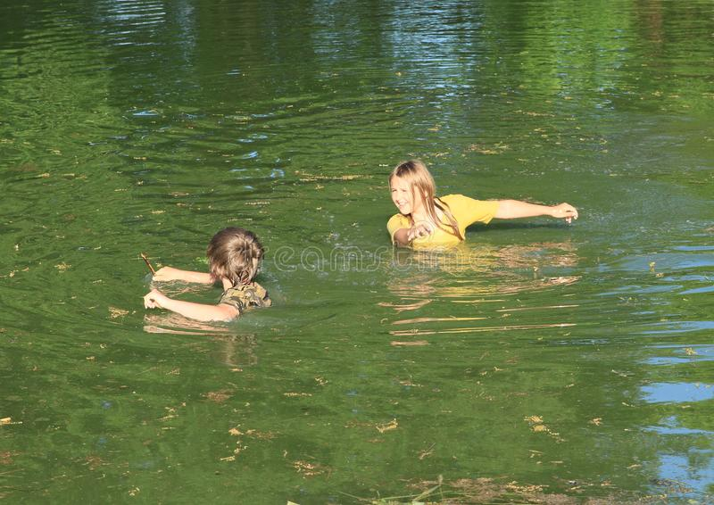 Nasty kids in clothes soaking wet in water. Nasty kids - girl and boy in clothes soaking wet in dirty water of pond stock images