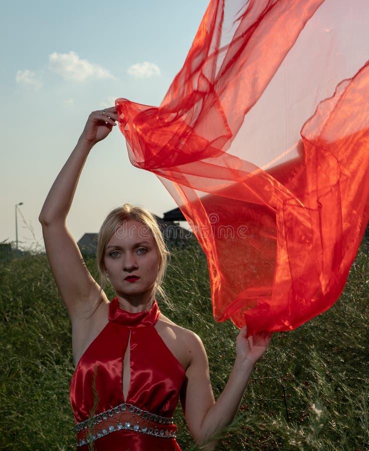 Natürlich schöne tausendjährige Frau im roten Kleid lizenzfreie stockfotos