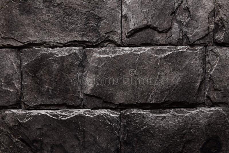 Natürliche Farbe des schwarzen braunen Steinwand-Beschaffenheitshintergrundes lizenzfreie stockfotos