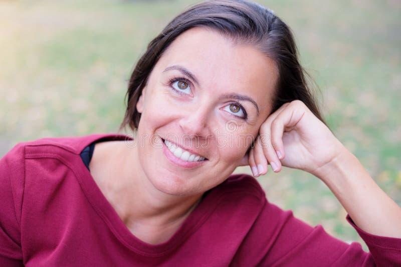 Natürliche Frau mit wunderndem Ausdruck in einem Park stockfotografie