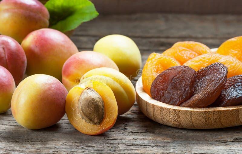 Natürliche getrocknete Aprikosen in der Bambusschüssel mit frischer ganzer reifer Aprikose auf hölzernem rustikalem Hintergrund stockfotografie