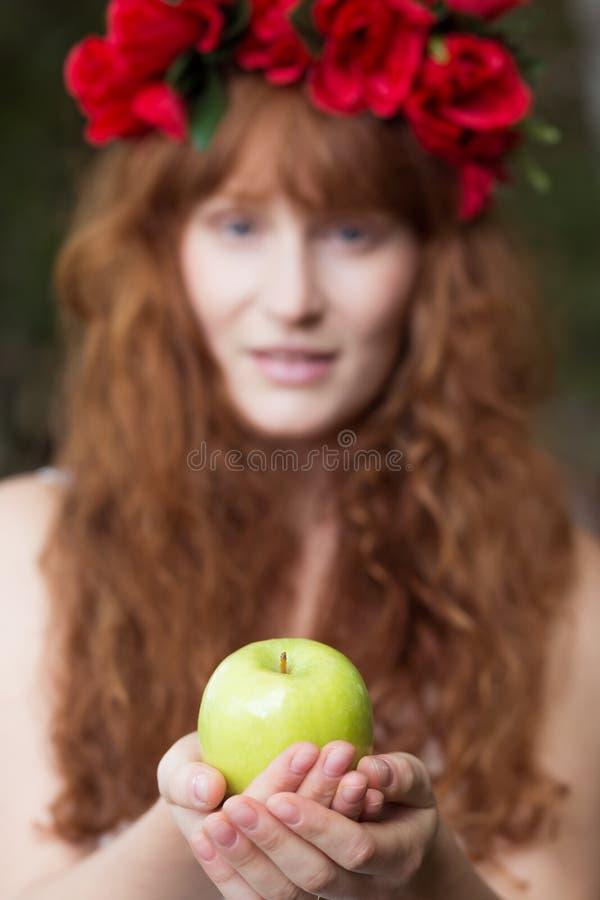 Natürliche junge Frau, die grünen Apfel hält stockbilder
