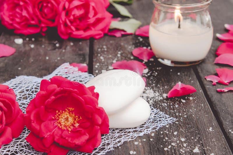 Natürliche kosmetische Seife mit roten Rosen und eine heiße Kerze auf einem dunklen hölzernen Hintergrund lizenzfreies stockfoto