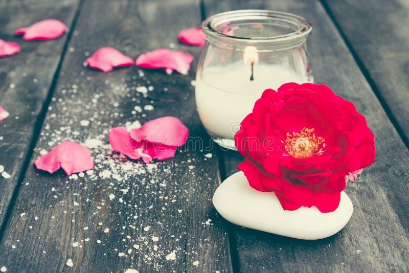 Natürliche kosmetische Seife mit roten Rosen und eine heiße Kerze auf einem dunklen hölzernen Hintergrund stockbild