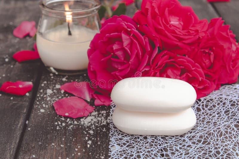 Natürliche kosmetische Seife mit roten Rosen und eine heiße Kerze auf einem dunklen hölzernen Hintergrund stockfotografie