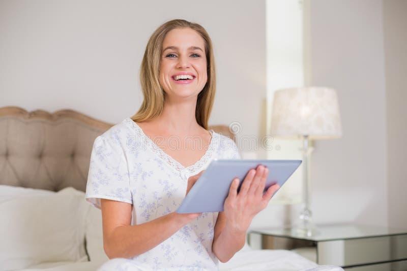 Natürliche lachende Frau, die auf dem Bett hält Tablette sitzt stockfotos