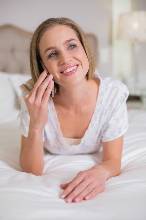 Natürliche lachende Frau, die am Bettanrufen liegt lizenzfreie stockbilder